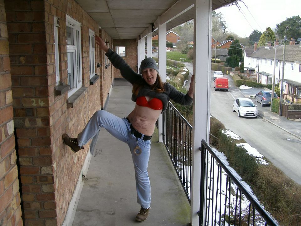 Joanna Dennehy poses for a photo with her top lifted and a pair of handcuffs on her belt while she was on the run for stabbin
