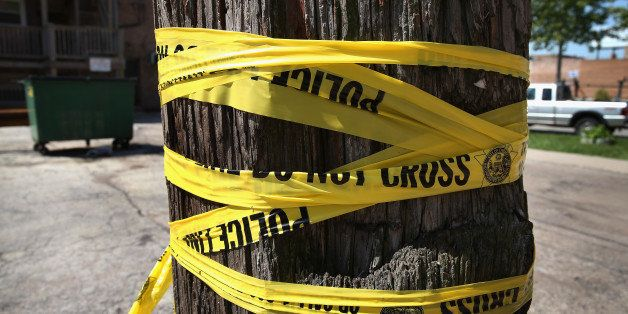 CHICAGO, IL - MAY 13:  Crime scene tape is wrapped around a power pole near the location where a 20-year-old man died from a