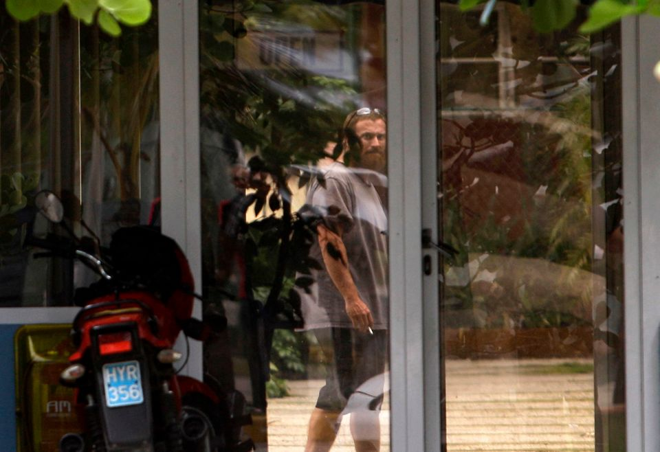 Joshua Michael Hakken stands behind a glass door at the Hemingway Marina in Havana, Cuba, Tuesday, April 9, 2013. Hakken and