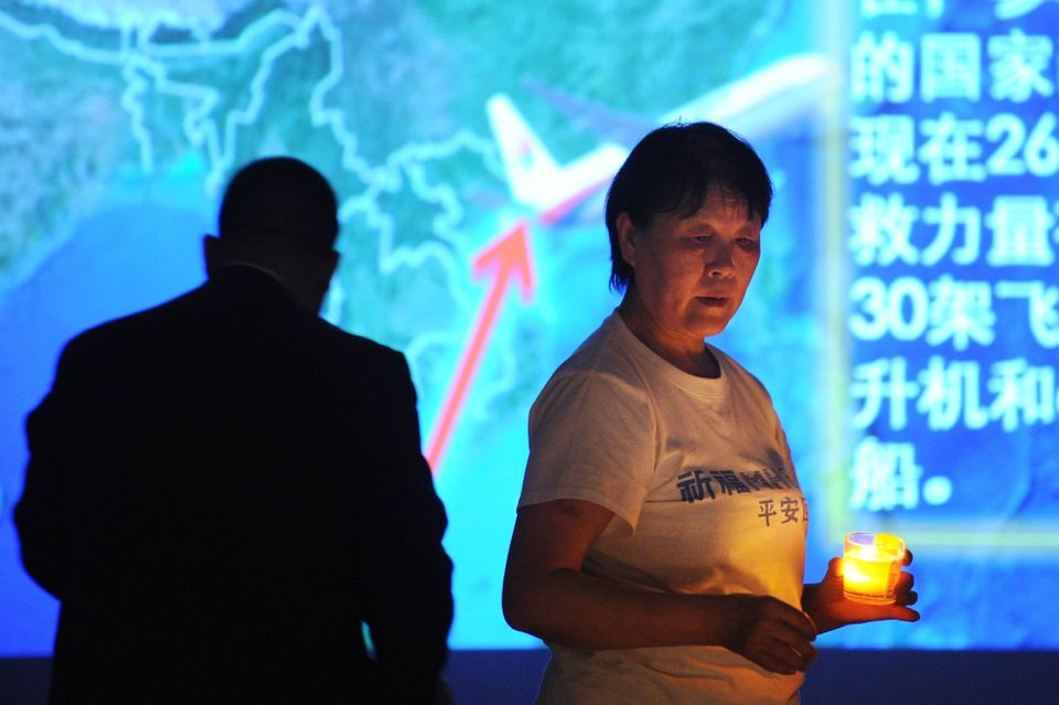 A Chinese relative of passengers on the missing Malaysia Airlines flight MH370 holds a candle as she takes part in a prayer s