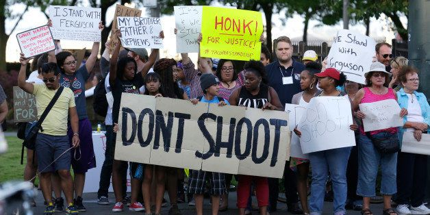 "Protesters hold a sign that reads ""Don't Shoot"" as they attend an evening rally Tuesday, Aug. 19, 2014, in Tacoma, Wash. Seve"