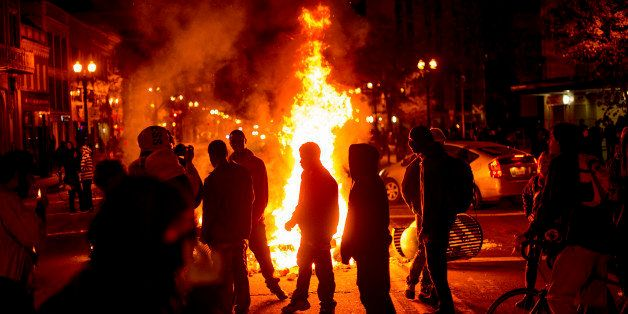 Protesters gather around burning refuse in Oakland, Calif., on Tuesday, Nov. 25, 2014, after the announcement that a grand ju