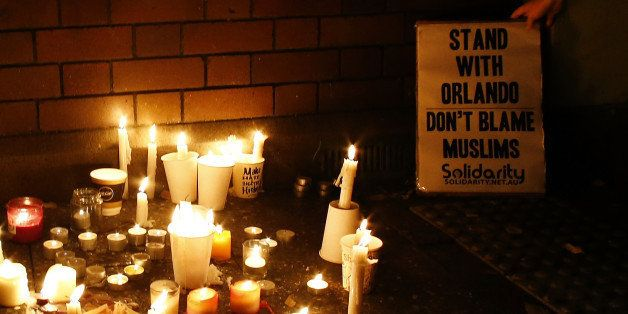 SYDNEY, AUSTRALIA - JUNE 13:  A woman places a banner next to the candles during a candlelight vigil for the victims of the P