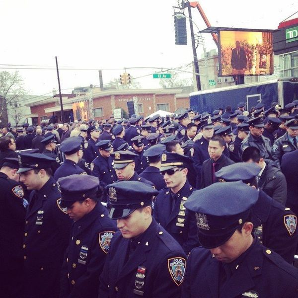 Some NYPD officers turn their backs while New York City mayor Bil de Blasio speaks at slain NYPD officer Wenjian Liu's funera
