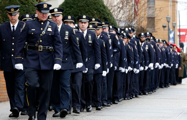 New York City police officers march before funeral services for police officer Wenjian Liu at Aievoli Funeral Home, Sunday, J