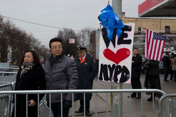 Pedestrians pause outside the funeral of New York Police Department officer Wenjian Liu at Aievoli Funeral Home, Sunday, Jan.