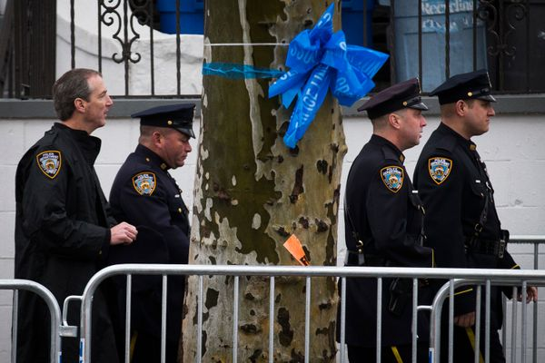Officers pass a blue ribbon as they arrive to the funeral of New York Police Department Officer Wenjian Liu at Aievoli Funera