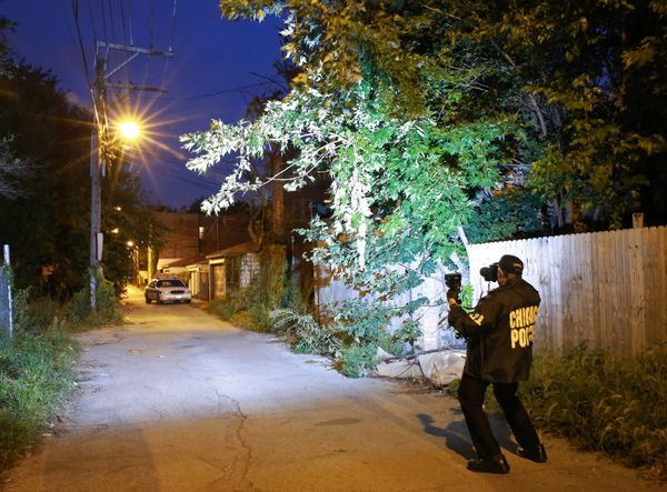 A Forensics Services investigator photographs the scene where a gunshot victim died, in an alley on the 4000 block of West Ja