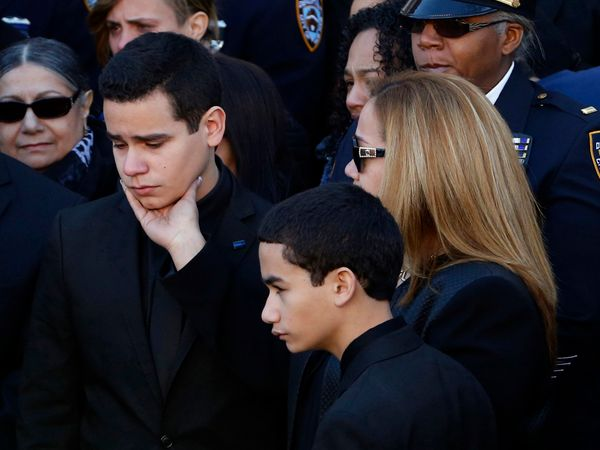Justin Ramos, the son of slain New York City police officer Rafael Ramos, left, is comforted by his mother, Maritza Ramos, fo