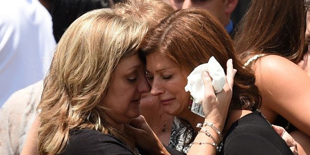 FRANKLIN, LA - JULY 27:  Dondie Breaux (R), mother of Maycie Breaux, is consoled outside of the Church of the Assumption on J