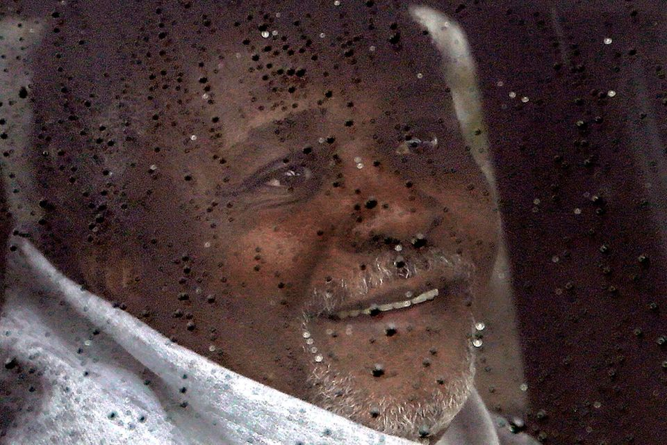 Alstory Simon, inside the passenger's seat, smiles through the window in the rain while leaving the Jacksonville Correction C