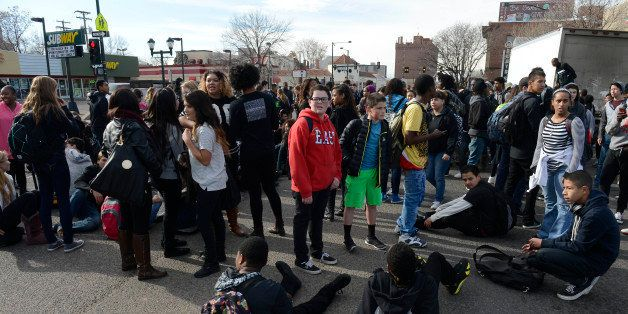 DENVER, CO - DECEMBER 03: East High School students gather and sit in the intersection of York St and Colfax Ave during a Fer
