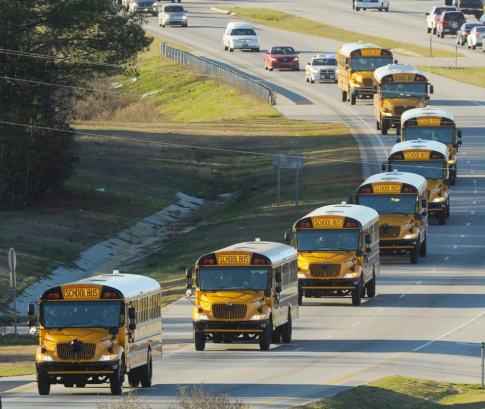 """The funeral procession of slain bus driver Charles """"Chuck"""" Poland makes its way down Highway 231 in Ozark, Ala., Sunday Over"""