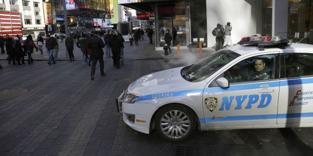 FILE. In this Jan. 8, 2015 file photo, a policeman looks out the window of his patrol car in Times Square in New York. In bus