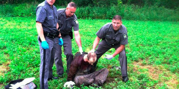 Police stand over David Sweat after he was shot and captured near the Canadian border Sunday, June 28, 2015, in Constable, N.
