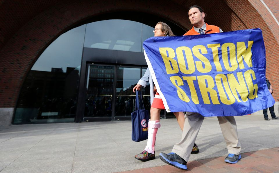 "Boston Marathon bombing volunteer first responder Carlos Arredondo holds a ""Boston Strong"" banner as he leaves the Moakley Fe"