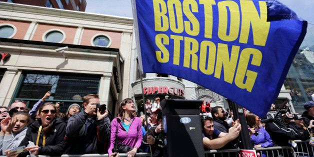 """Race fans with a """"Boston Strong"""" flag cheer for competitors near the finish line of the 118th Boston Marathon, Monday, April"""
