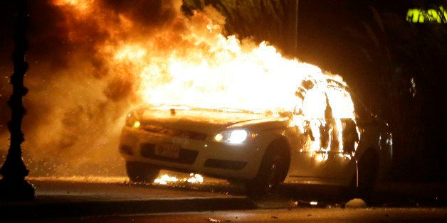 A police car is set on fire after a group of protesters vandalize the vehicle after the announcement of the grand jury decisi
