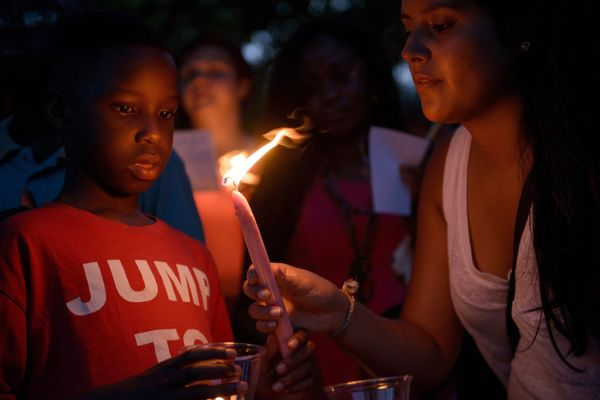 People participate in a candle light vigil at Marion Square near the Emanuel AME Church in Charleston, South Carolina on June