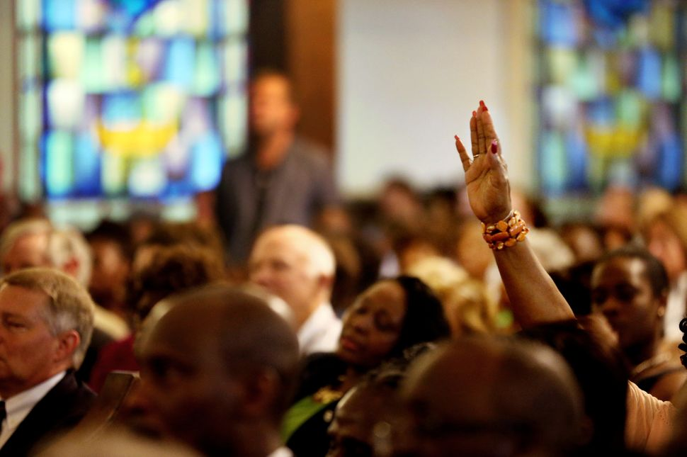 Hands are raised during a prayer vigil held at Morris Brown AME Church in New York City for the victims of Wednesday's shooti