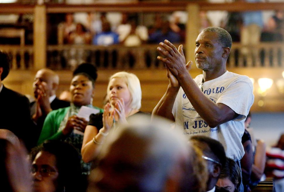The crowd applauds during a prayer vigil held at Morris Brown AME Church in New York City for the victims of Wednesday's shoo