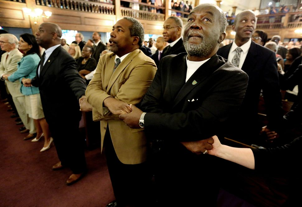 From left, Reverend Richard Harkness holds hands with Reverend Jack Lewin during a prayer vigil held at Morris Brown AME Chur