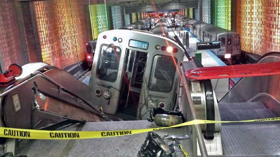 A Chicago Transit Authority train car rests on an escalator at the O'Hare Airport station after it derailed early Monday, Mar