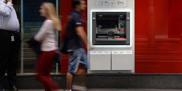 People walk past an ATM machine of Australian banking giant Westpac in the central business district of Sydney on November 3,