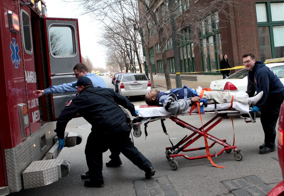 Police and emergency personnel transport a man to an ambulance after a shooting at Stephens Institute of Business and Arts on