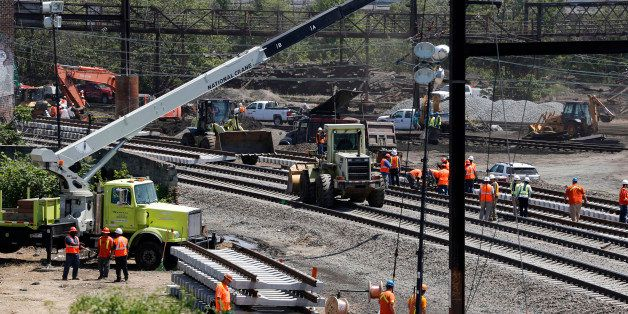 Workers labor on the site where a deadly train derailment occurred earlier in the week, Friday, May 15, 2015, in Philadelphia