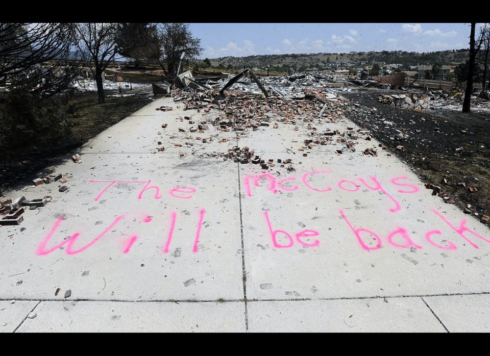 A message is displayed on a driveway near the remains of a home in the Mountain Shadows neighborhood of Colorado Springs, Col