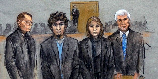 In this courtroom sketch, Dzhokhar Tsarnaev, second from left, is depicted standing with his defense attorneys William Fick,