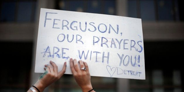 A participant holds a sign at a prayer vigil for Michael Brown outside the McNamara Federal Building in Detroit Monday, Aug.