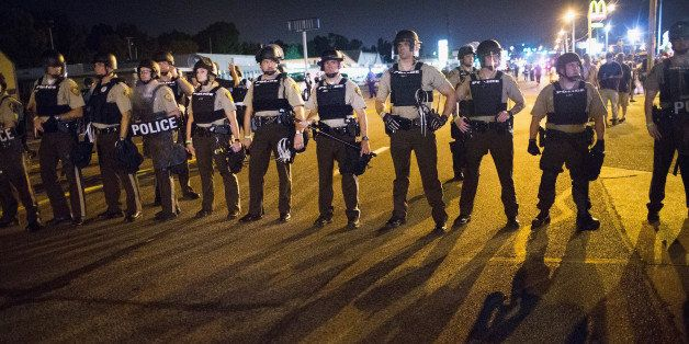 FERGUSON, MO - AUGUST 10:  Police stand guard as demonstrators, marking the one-year anniversary of the shooting of Michael B