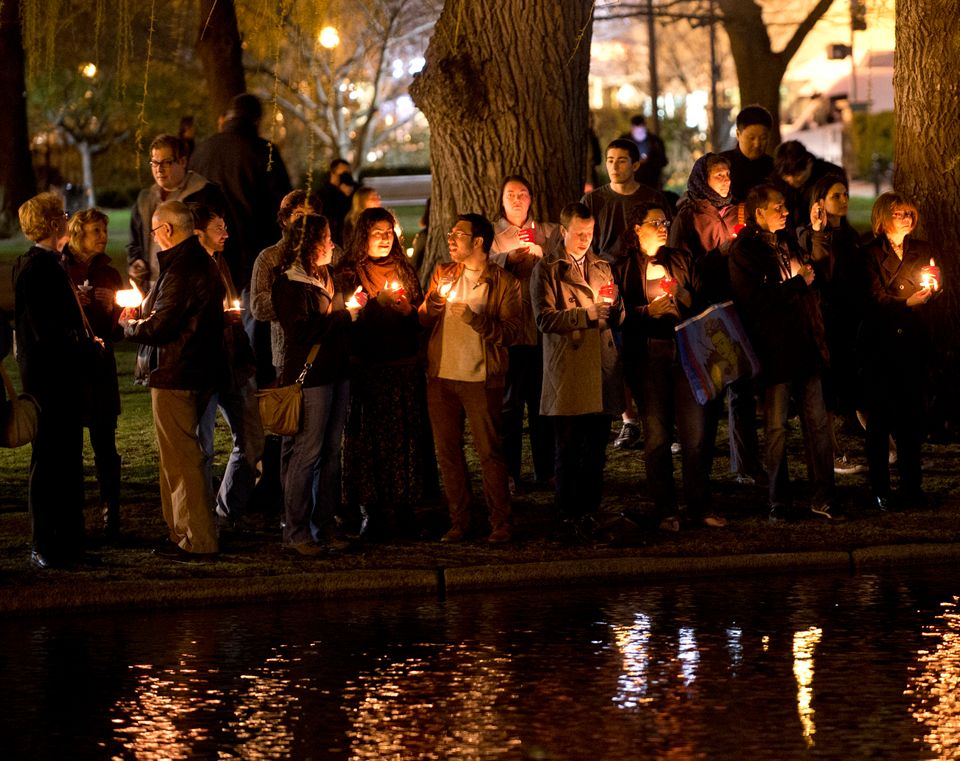 Mourners gather on the edge of the pond in the Boston Public Gardens for a candle light vigil April 16, 2013 in Boston. A few