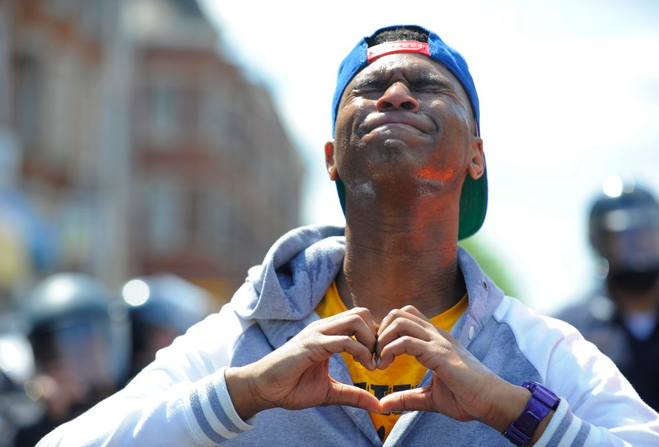 Devante Hill makes a heart with his hands after he was hit with pepper spray after someone threw a bottle at police on Tuesda