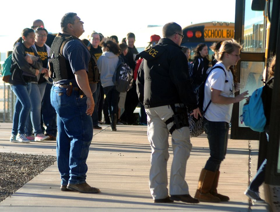 Authorities stand guard as students are escorted from Berrendo Middle School after a shooting, Tuesday, Jan. 14, 2014, in Ros