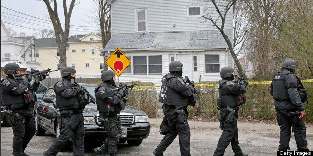 WATERTOWN, MA - APRIL 19: A SWAT team files down Nicholas Avenue during an ongoing manhunt for a suspect in the terrorist bom