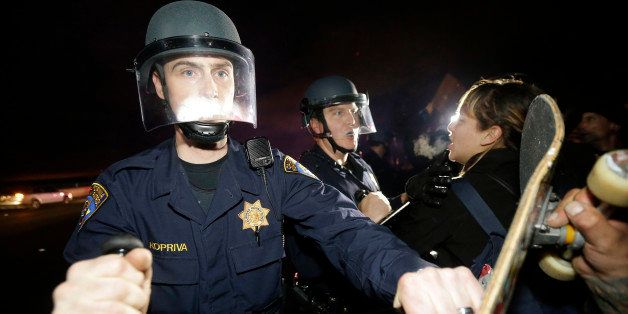 California Highway Patrol officers push back protesters who blocked Highway 80 in response to police killings in Missouri and