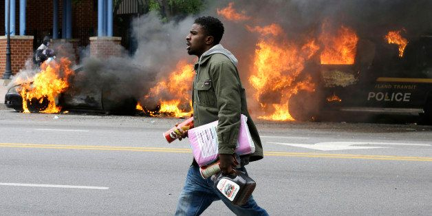 A man carries items from a store as police vehicles burn, Monday, April 27, 2015, after the funeral of Freddie Gray in Baltim