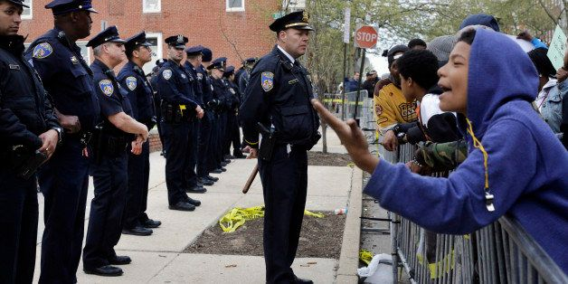 Members of the Baltimore Police Department stand guard outside the department's Western District police station during a prot