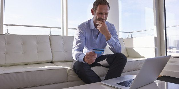 Man using laptop and credit card.