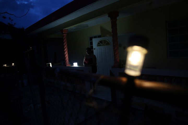 Jannet Rodriguez, 40, stands on the porch of her darkened house in Adjuntas, Puerto Rico, on May 11, 2018. Hurricane Maria le