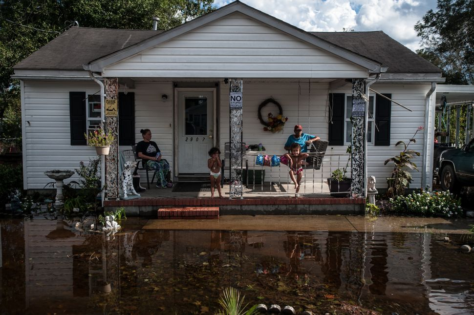 Gloria Freeman and her children, Bella and Cullen Jr., sit on their porch with Johnny Oxdine as floodwaters fill their yard i