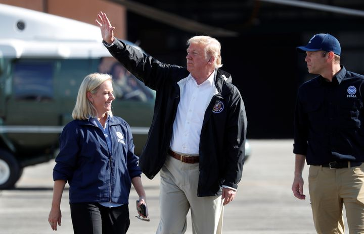 President Donald Trump waves as FEMA Director Brock Long and Homeland Security Secretary Kirstjen Nielsen walk Trump to Air F