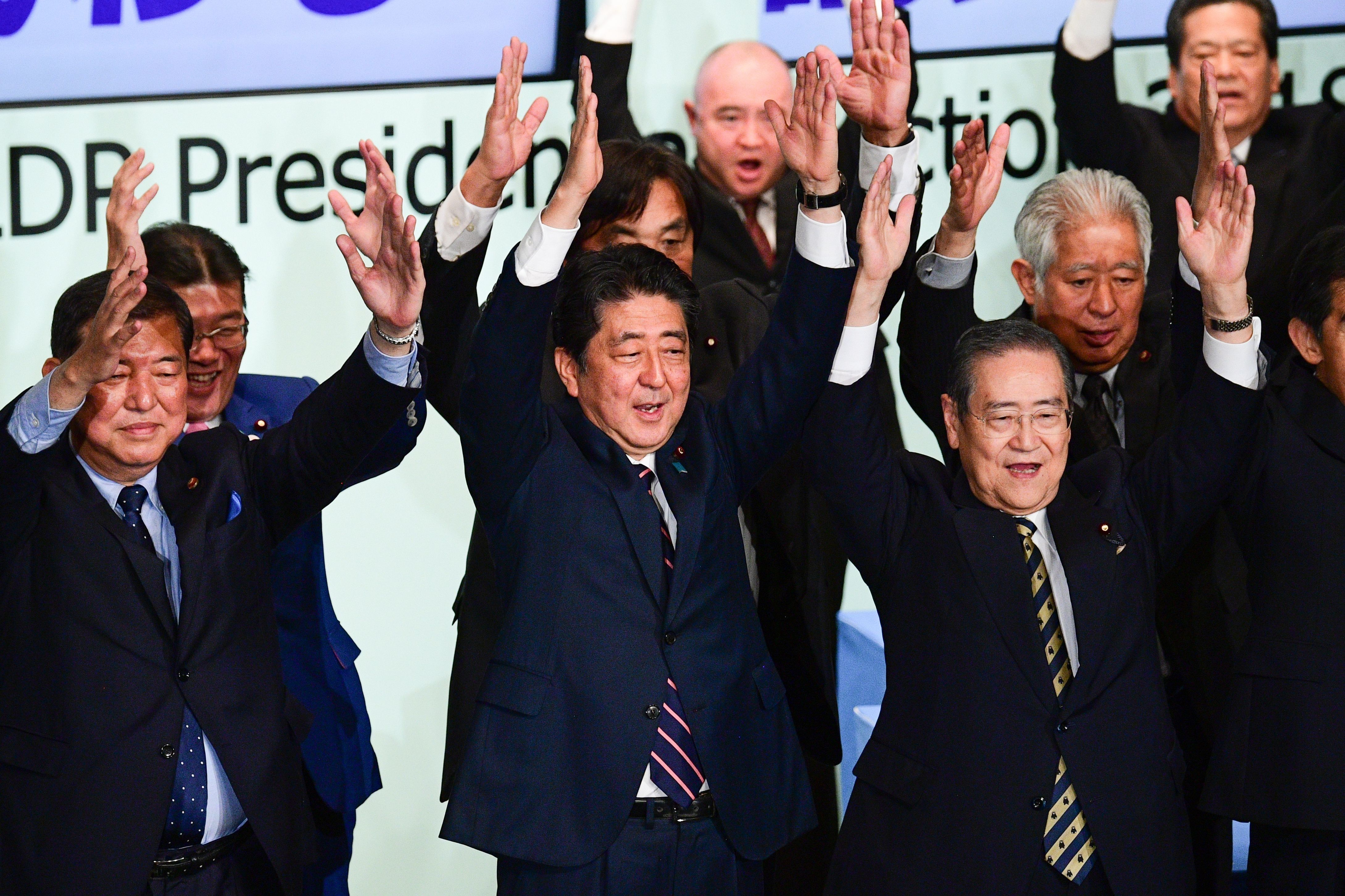 Japan's Prime Minister Shinzo Abe (C) celebrates after the ruling liberal Democratic Party (LDP) leadership election at the party's headquarters in Tokyo.