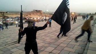 A fighter of the Islamic State of Iraq and the Levant (ISIL) holds an ISIL flag and a weapon on a street in the city of Mosul, Iraq June 23, 2014. REUTERS/Stringer/File Photo
