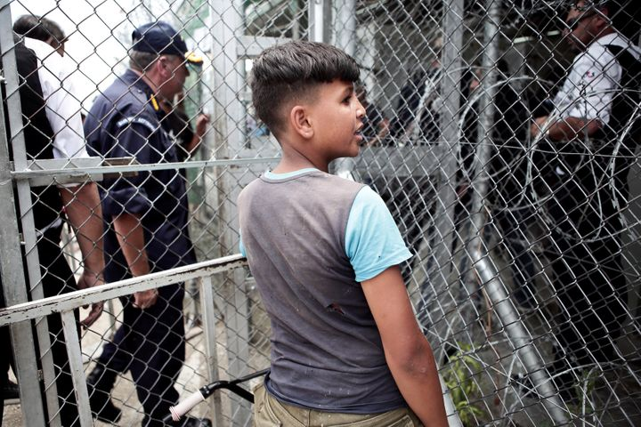 A migrant boy stands next to a metal fence at the Moria camp for refugees and migrants on the island of Lesbos, June 27, 2018