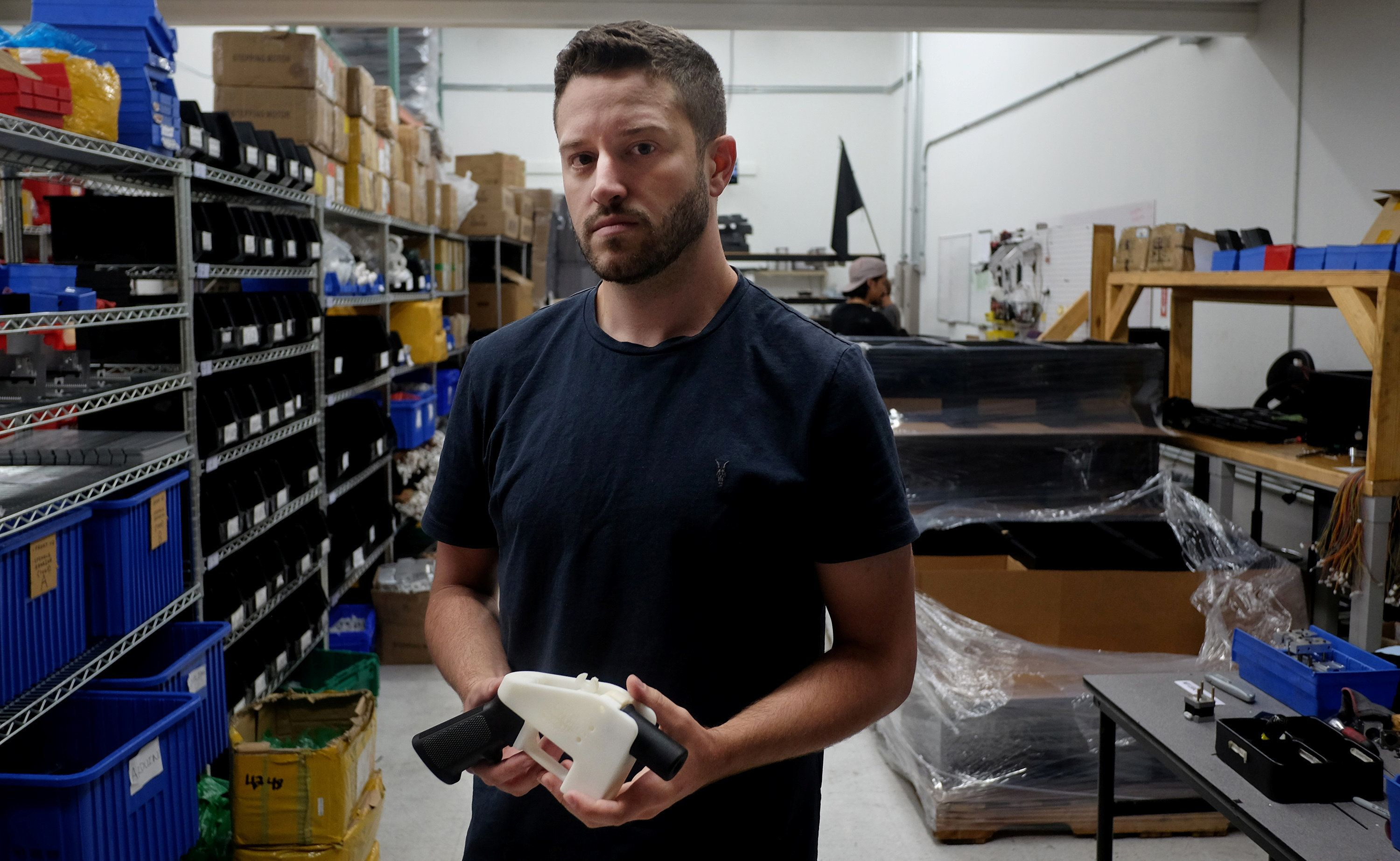 """Cody Wilson poses with an example of a 3-D printed gun, called the """"Liberator,"""" which his company Defense Distributed designs at his factory in Austin, Texas, U.S. August 1, 2018. Picture taken August 1, 2018.   REUTERS/Kelly West"""