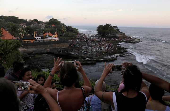 Tourists take pictures of the Hindu temple Tanah Lot (R) in Tabanan, on the resort island of Bali, Indonesia May 6, 2018.